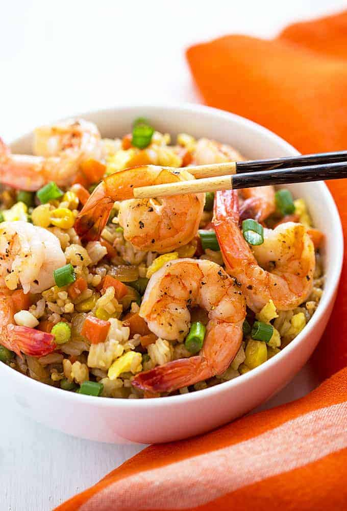 A chopstick holding a shrimp in a white bowl of shrimp fried rice.