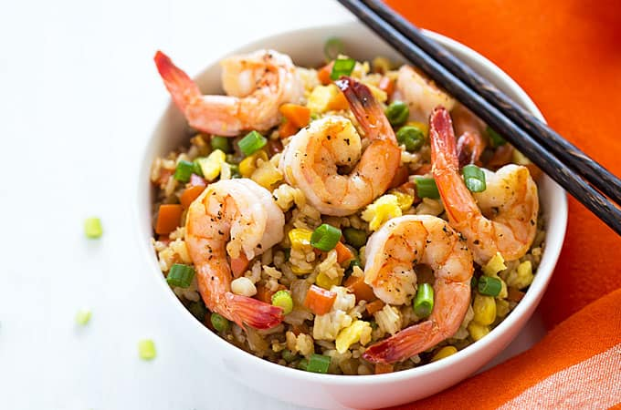 Overhead view of a bowl of shrimp fried rice with chopsticks by an orange napkin.