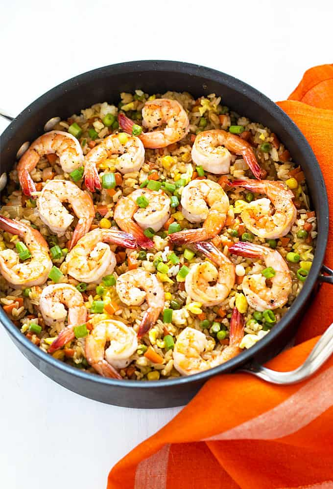 Overhead view of easy shrimp fried rice in a skillet by an orange napkin.