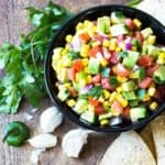 Avocado, Corn and Tomato Salsa in a round black bowl
