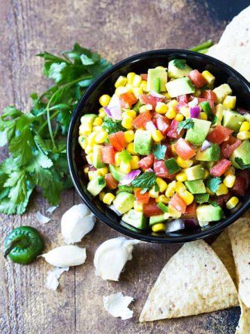 Avocado, Corn and Tomato Salsa in a round black bowl