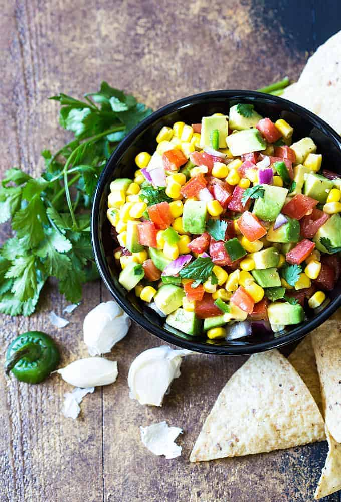 Overhead view of Avocado, Corn and Tomato Salsa with onion, jalapeno and cilantro in a bowl