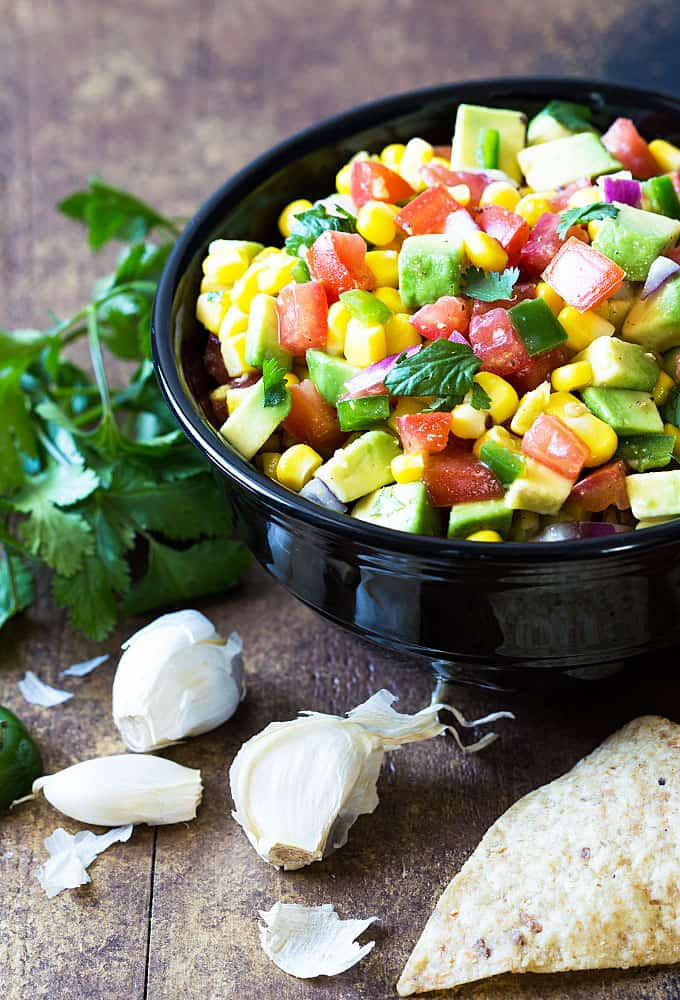 Salsa with avocado, tomatoes, corn, onion and cilantro in a round black bowl with tortilla chips