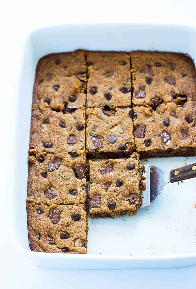 Chocolate chip bars that have been cut into squares in a baking dish with a spatula.