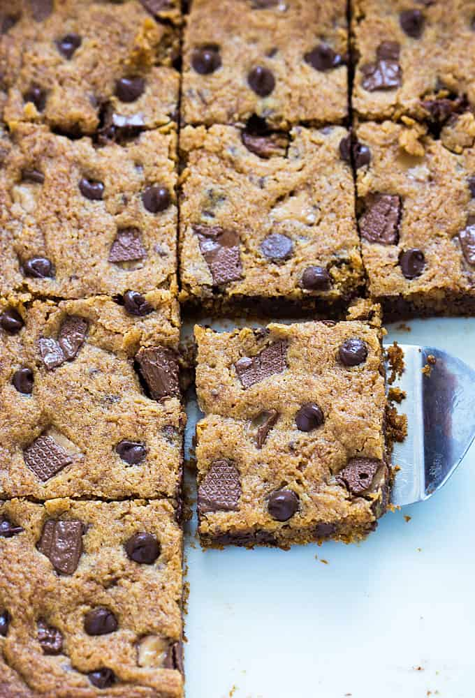 An overhead closeup of toffee bars in a baking dish with a spatula.