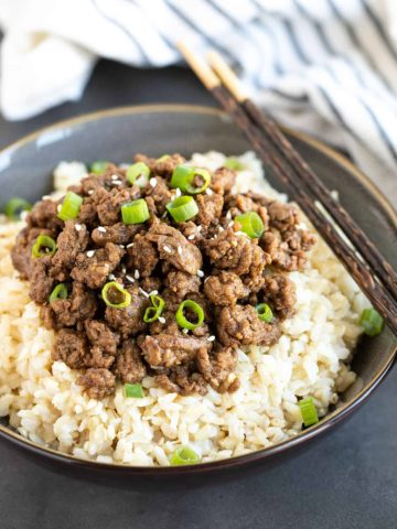 A bowl of rice topped with ground beef and green onions with a set of chopsticks.