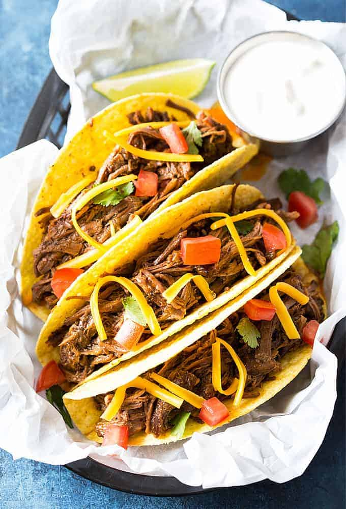 Overhead view of three shredded beef tacos in a basket with parchment paper.