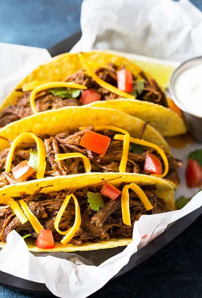 Closeup view of three shredded beef hard tacos.