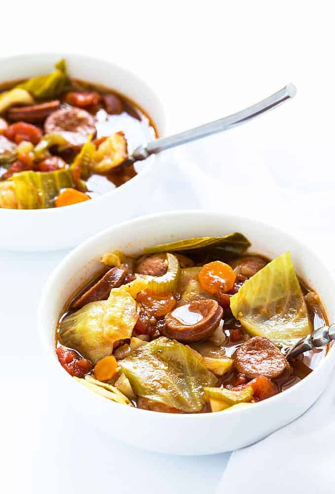 Two white bowls of sausage and cabbage soup on a white surface.