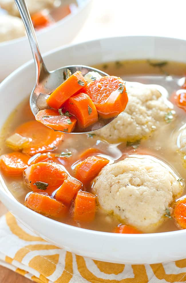A white bowl soup with matzo balls and carrots with a spoon.