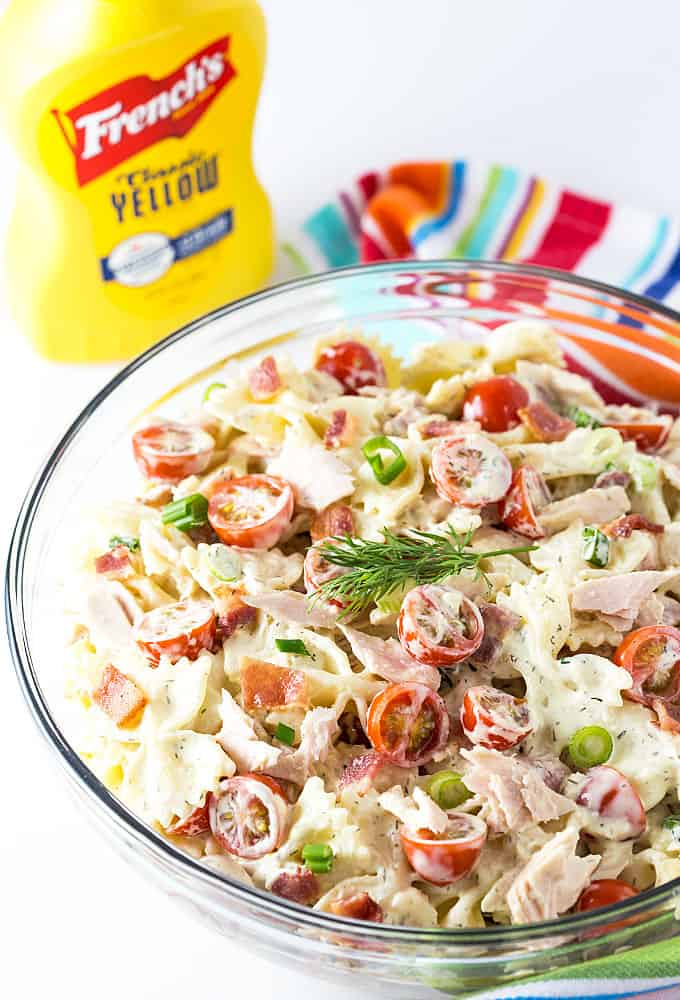 A bowl of tuna and bacon pasta salad.  A bottle of mustard is in the background.