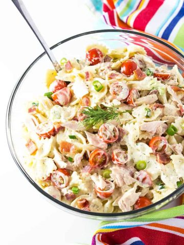 Overhead view of a glass bowl of pasta salad with a spoon by a striped towel.
