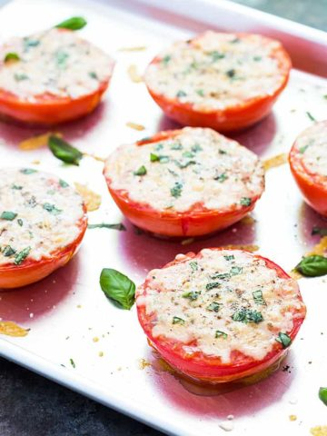 Baked Parmesan tomatoes topped with basil on a baking sheet.