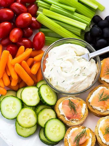 Overhead view of a bowl of cream cheese spread on a platter with vegetables.