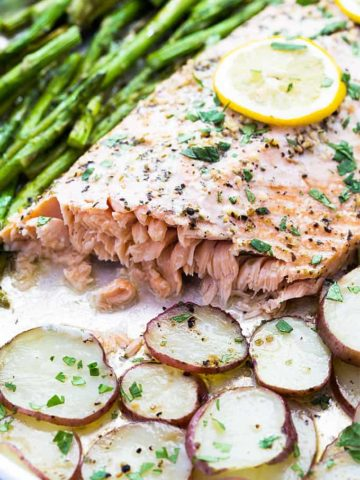 A closeup of baked salmon with potatoes and asparagus in a sheet pan.