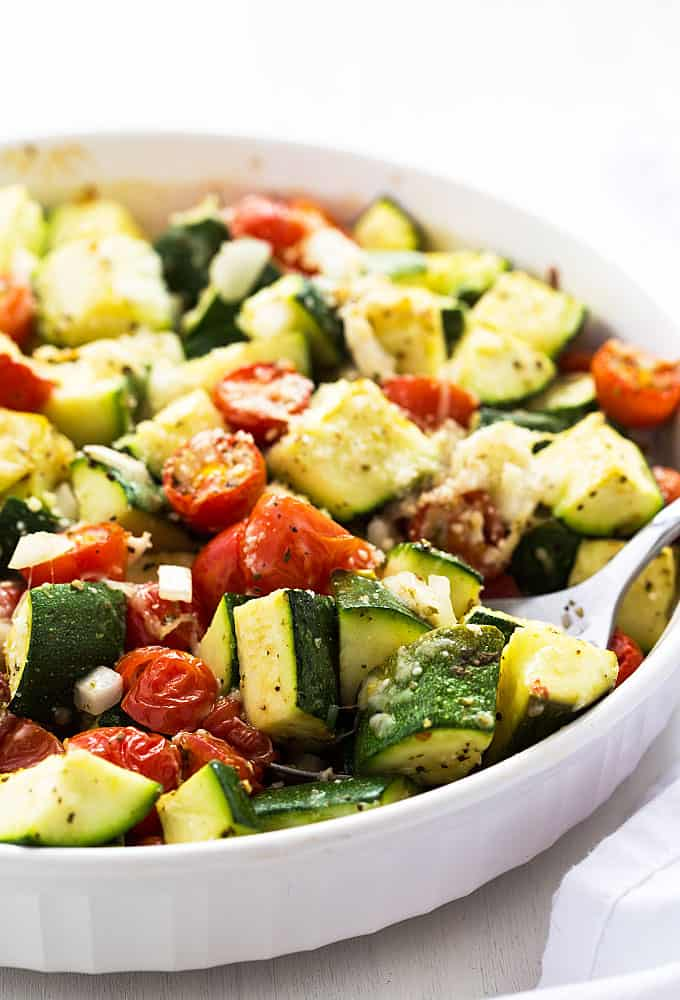 Front view of baked zucchini, tomatoes and onions in a baking dish with a spoon.