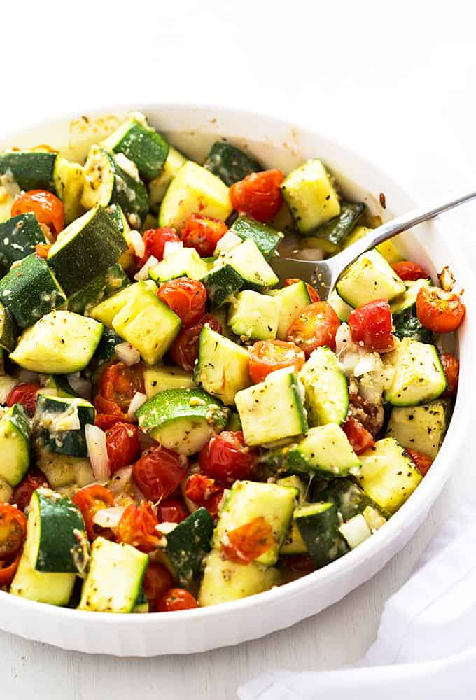 Italian zucchini, tomatoes and onions in a white baking dish with a serving spoon.