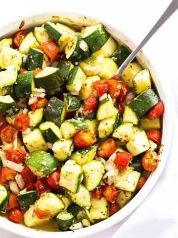 Overhead view of baked zucchini, tomatoes and onions in a white baking dish.