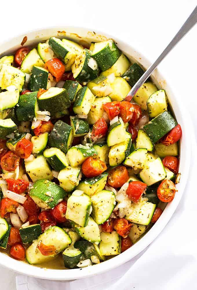 Overhead view of baked Italian zucchini and vegetables in a white baking dish with a spoon.