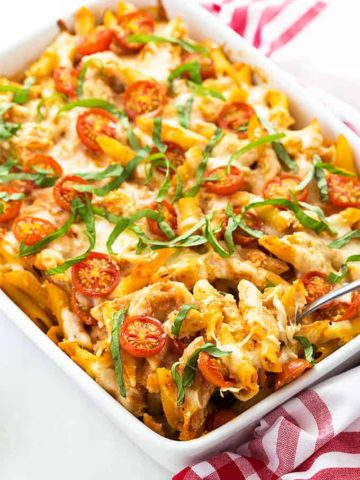 Chicken caprese pasta casserole topped with basil in a white baking dish.
