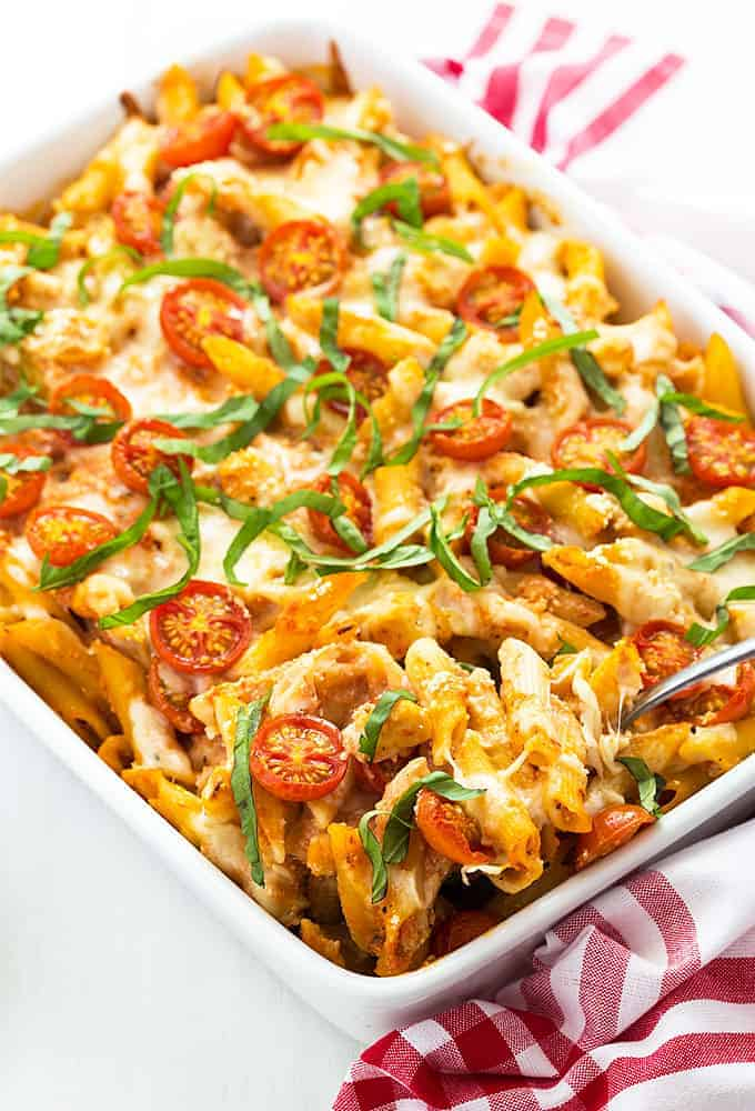 Chicken Caprese Pasta Casserole in a white baking dish beside a red and white kitchen towel