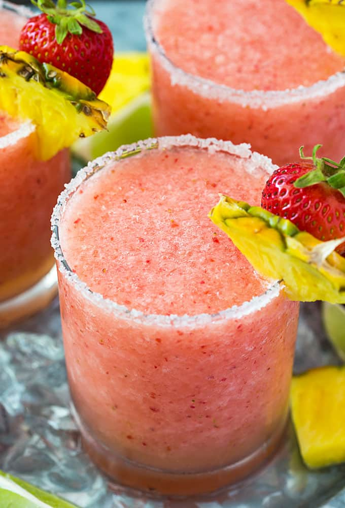Closeup of a frozen margarita garnished with a strawberry and pineapple slice.