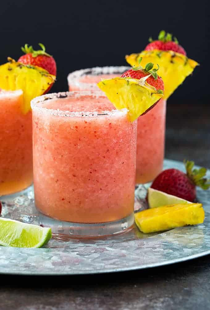 Front view of three frozen pineapple strawberry margaritas on a serving tray.
