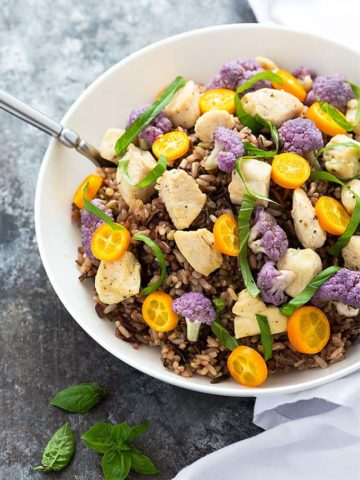 Overhead view of bite size chicken, purple cauliflower and sliced kumquats over rice in a bowl.
