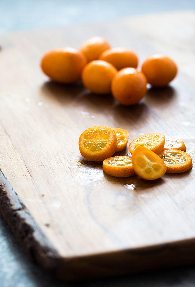 Sliced Kumquats on a wooden cutting board.