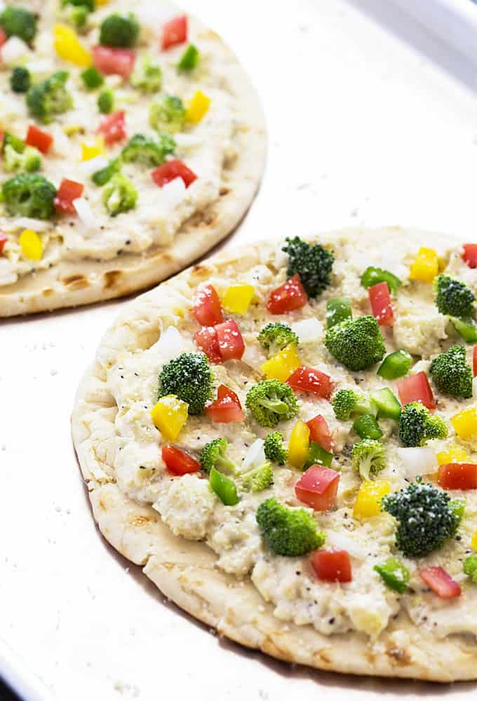 A closeup of flat bread topped with cheese spread and vegetables.