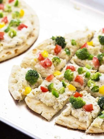 A closeup of flatbread topped with cheese spread and vegetables on a baking sheet.
