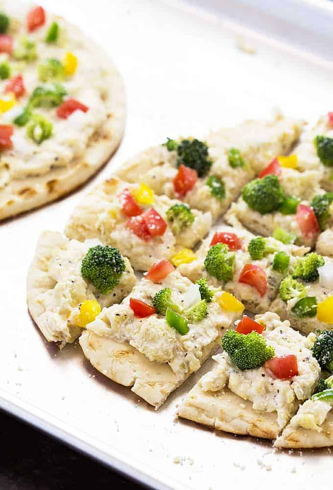 A closeup view of sliced cheesy flatbread topped with broccoli, onions and peppers.