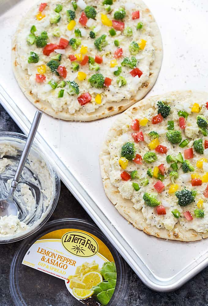 Overhead view of two flatbread with a cheese spread and veggies on a baking sheet.