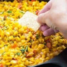 A tortilla chip being dipped into hot corn dip in a cast iron skillet.