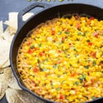 Hot corn dip in a cast iron skillet with overlay text.