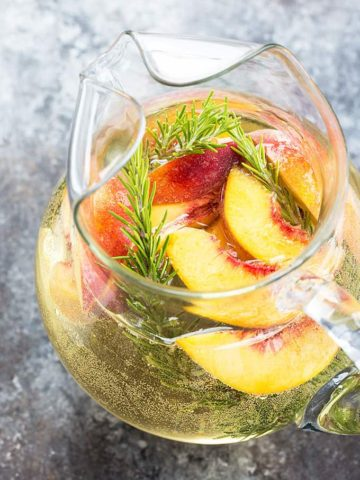 An angled overhead view of white sangria with peaches and rosemary in a pitcher.