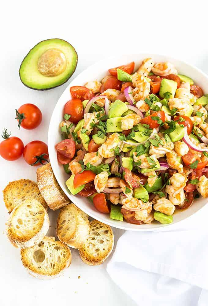 Overhead view of shrimp, avocado, tomato and onion salad in a white bowl.