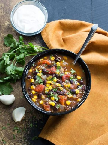 Overhead view of a black bowl of black bean, corn and tomato soup by an orange napkin.