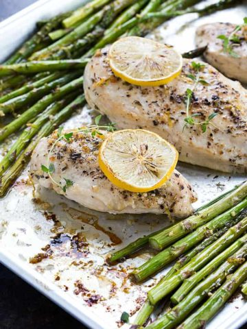 Baked boneless chicken breasts and asparagus spears on a baking sheet.