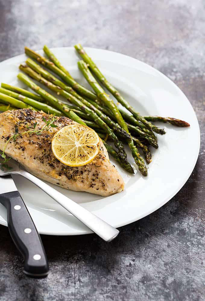 A baked chicken breast and asparagus spears on a white plate.