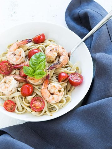 Overhead view of buttery shrimp over pesto pasta with tomatoes in a white bowl.