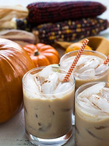 Three glasses of white russians by decorative pumpkins.