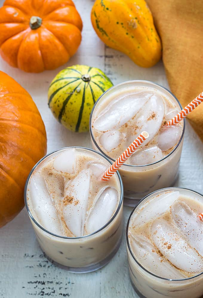 Overhead view of three white russians with straws by pumpkins.