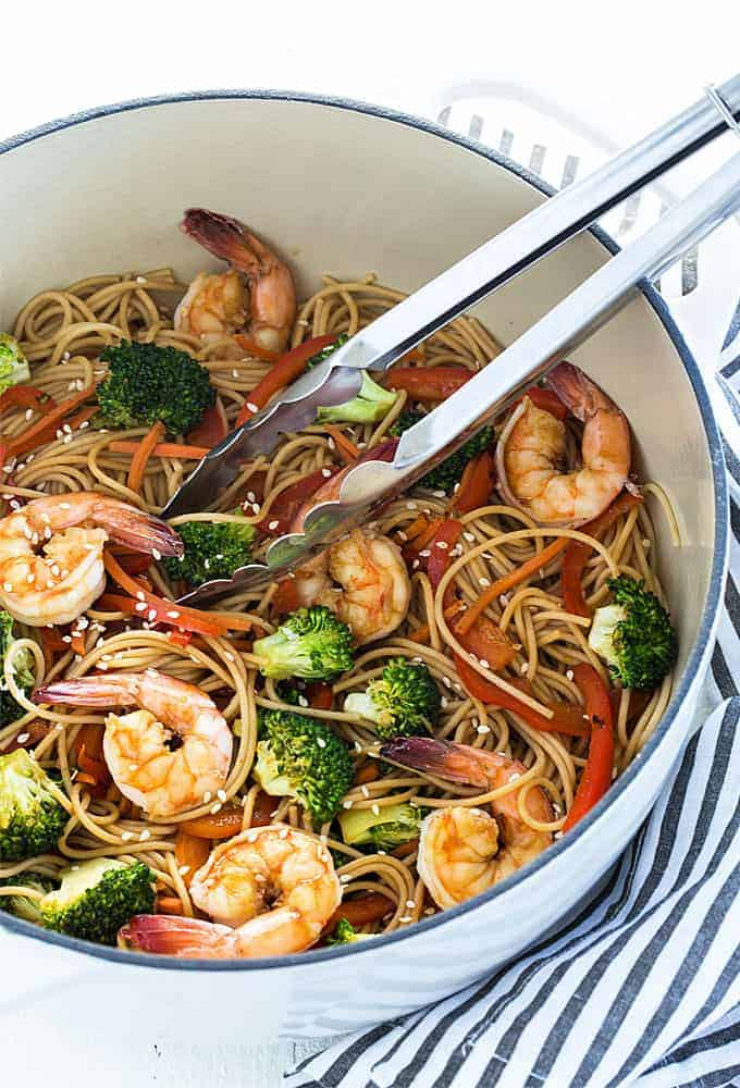 Shrimp lo mein with broccoli in a white dutch oven with a pair of tongs.