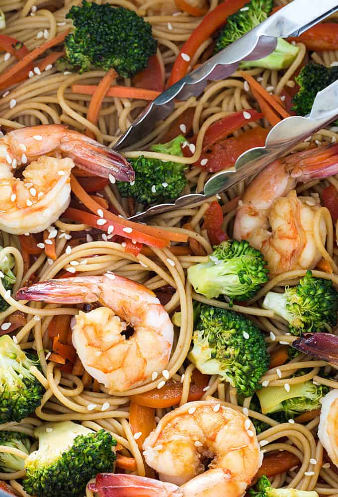 A closeup of shrimp and broccoli lo mein with a pair of tongs.