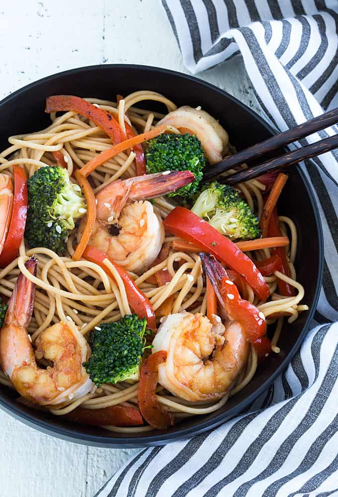 Shrimp and broccoli lo mein in a black bowl with a pair of chopsticks.