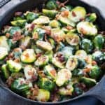 Baked brussels sprouts with cheese and bacon in a cast iron skillet.