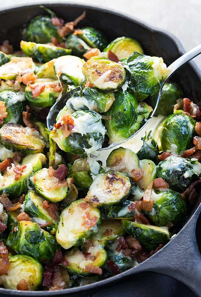 A closeup of baked cheesy brussels sprouts in a spoon.