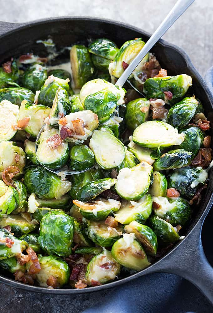 A spoon spooning cheesy brussels sprouts with bacon from a cast iron skillet.