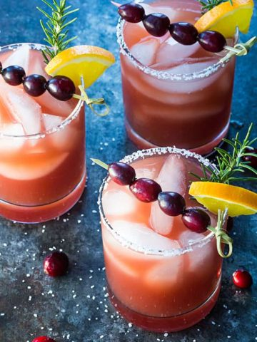 Three margaritas garnished with cranberries, orange and rosemary on a dark surface.